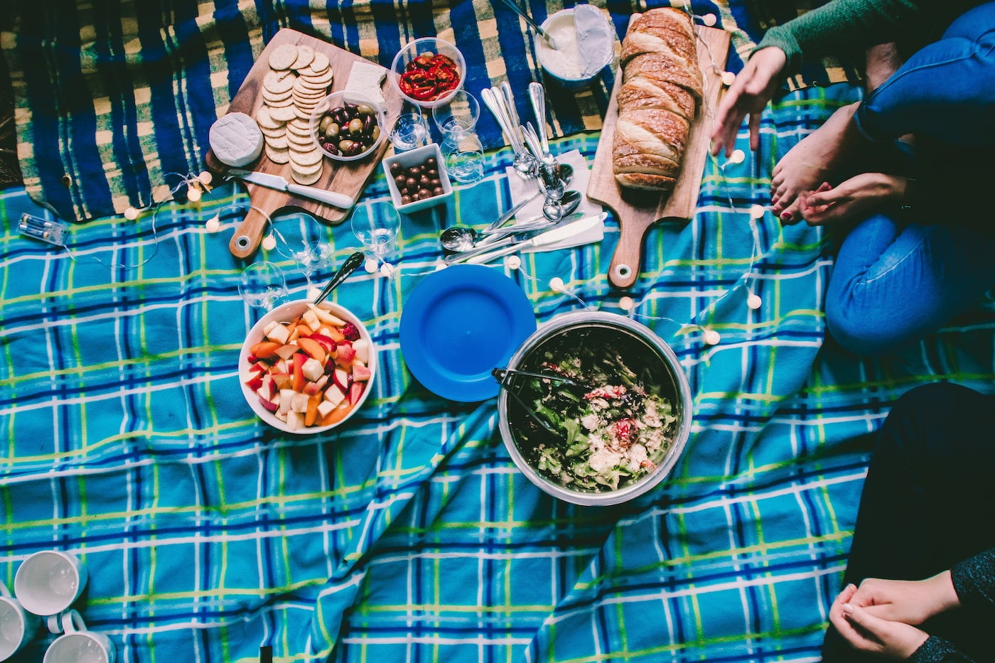 Charcuterie picnic on blankets outdoors.