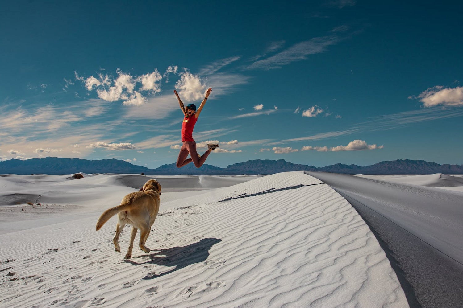 woman jumping on white sands dune with dog chasing her