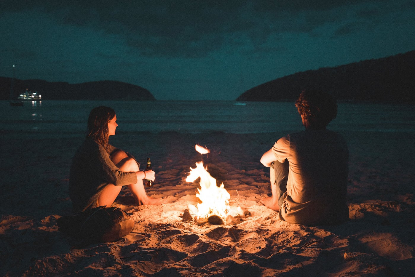 A couple hanging out around a campfire.