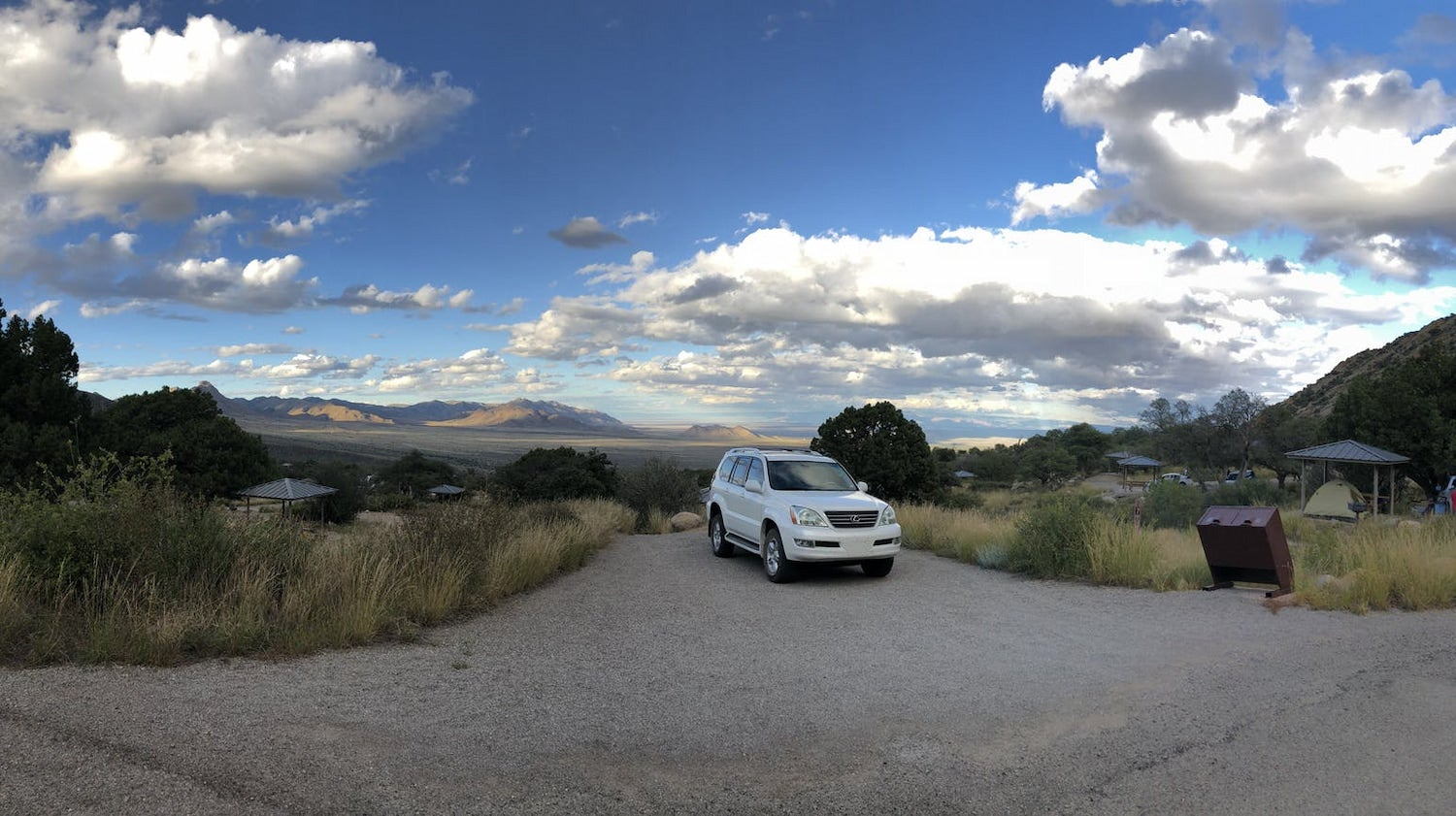 car parked at campground with beautiful vista in the background