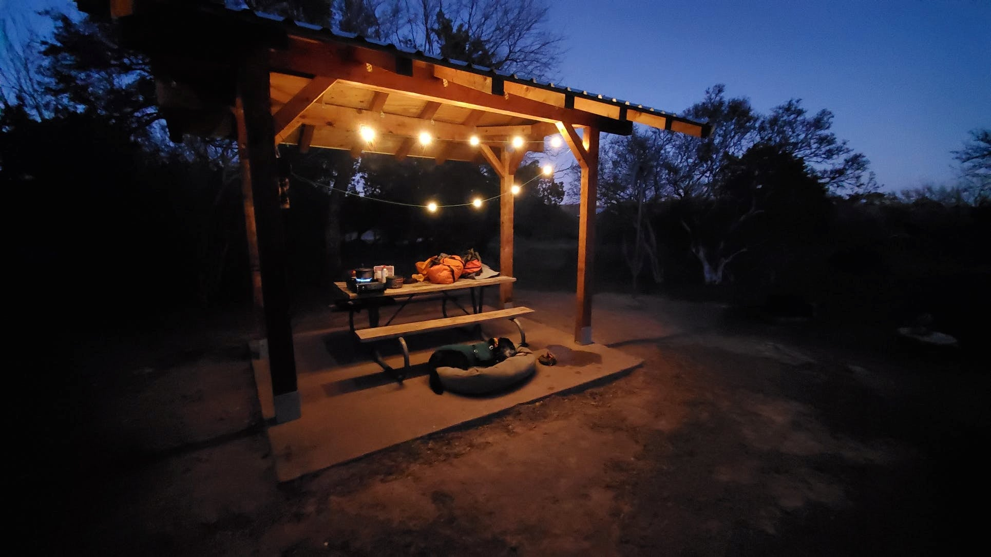 String lights in small awning over picnic table at campsite.