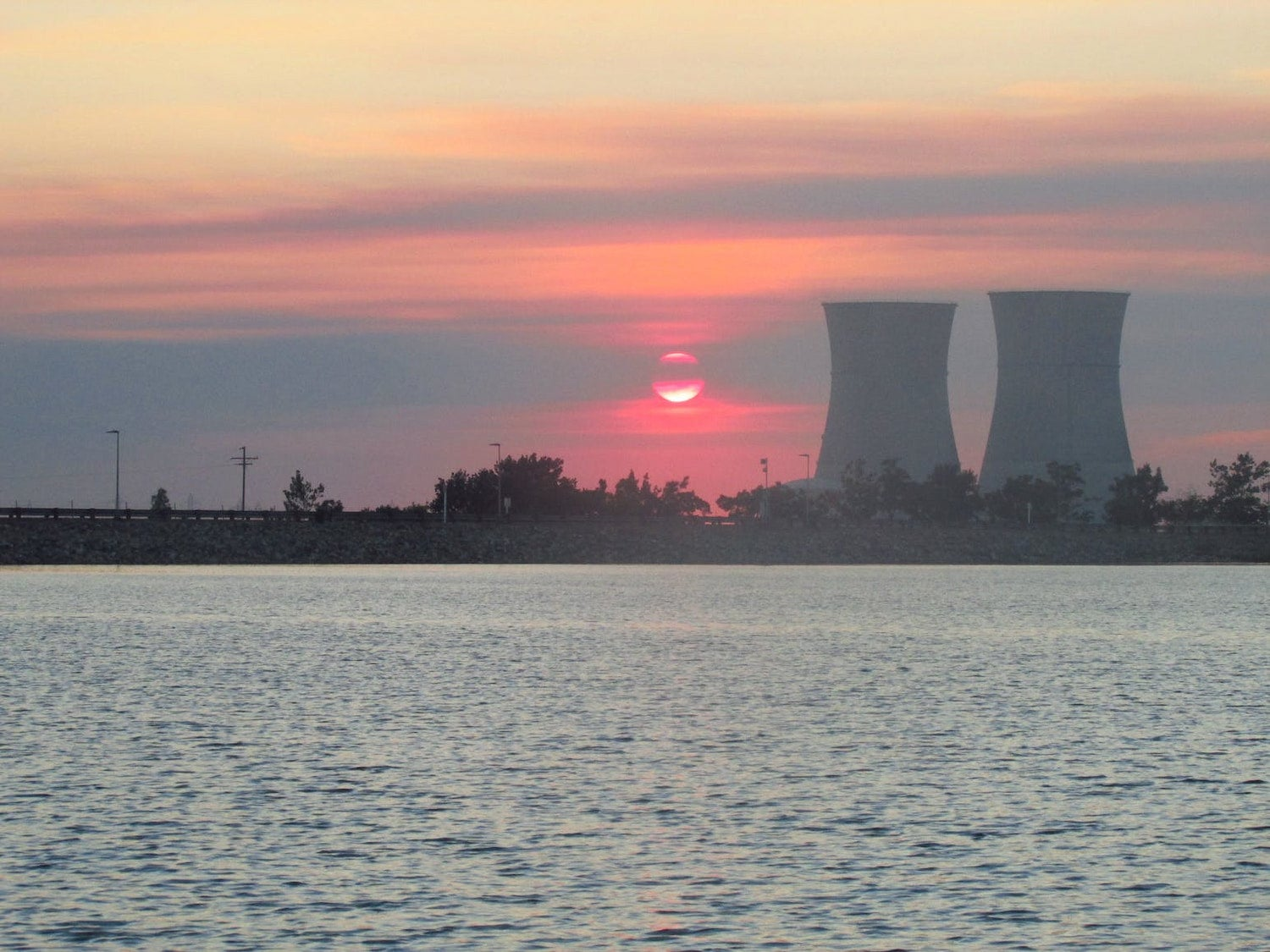 sunset over the water next to cooling towers