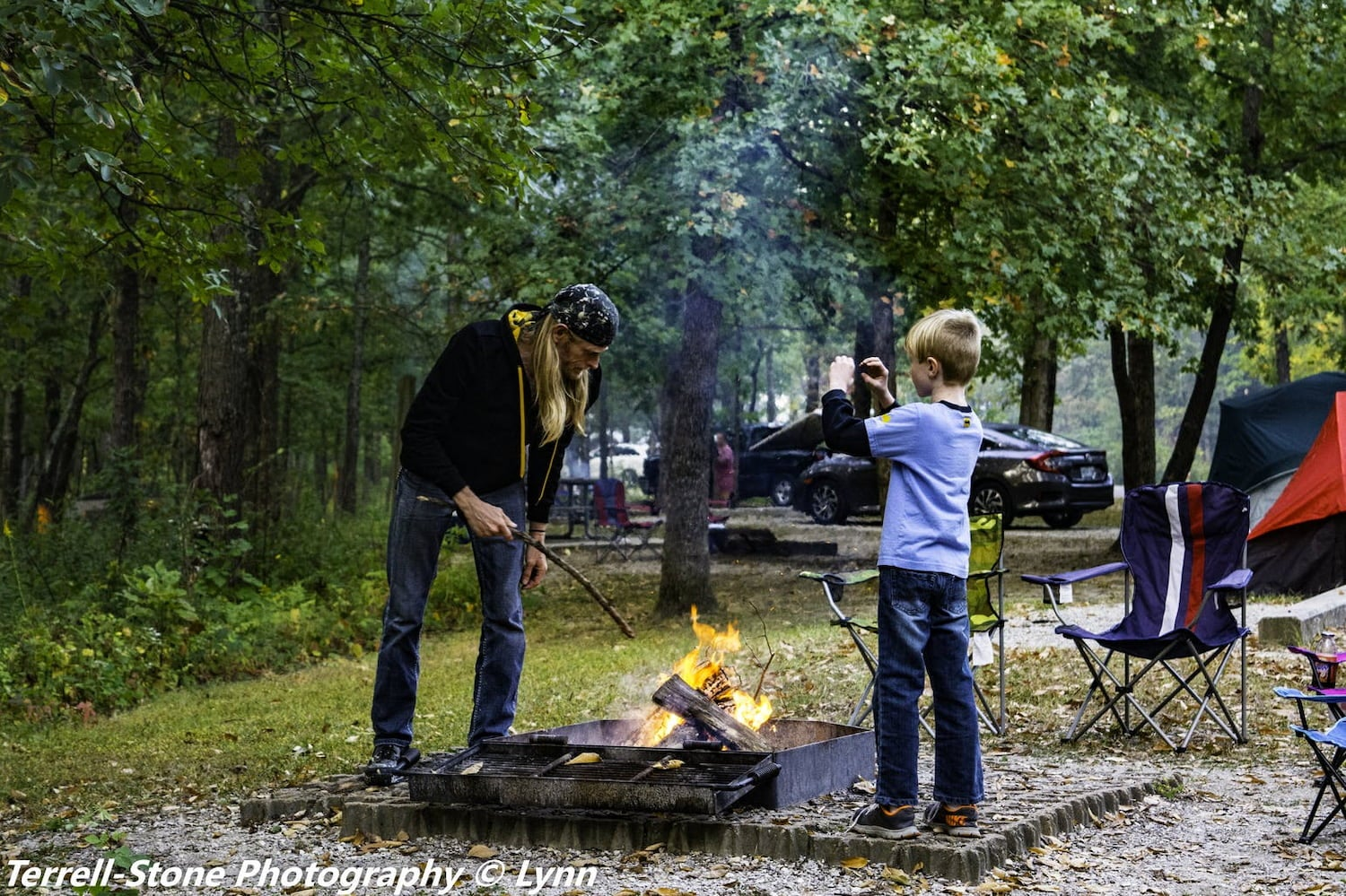 father and son tending the fire at a campsite