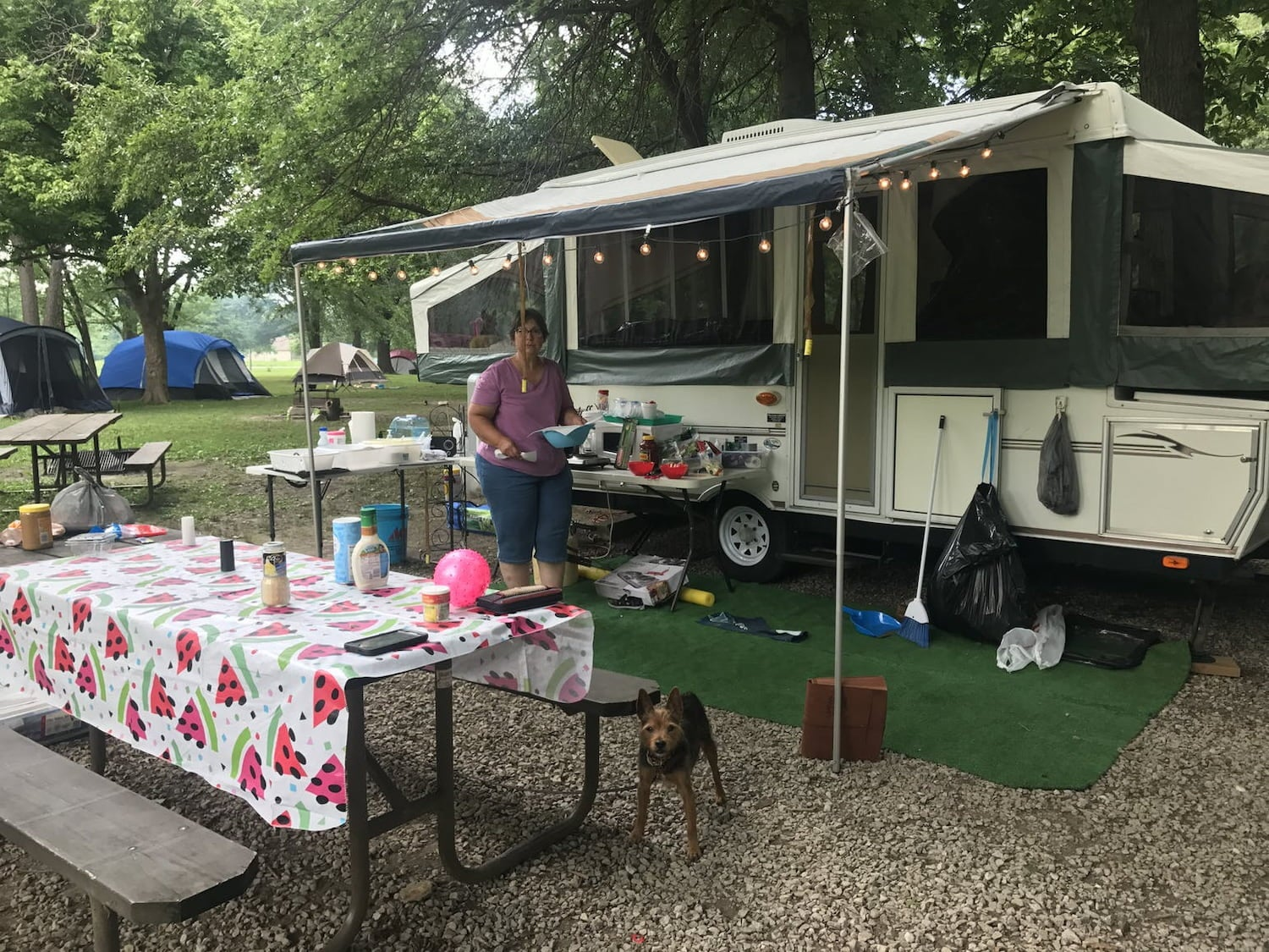 woman next to her trailer parked at campsite