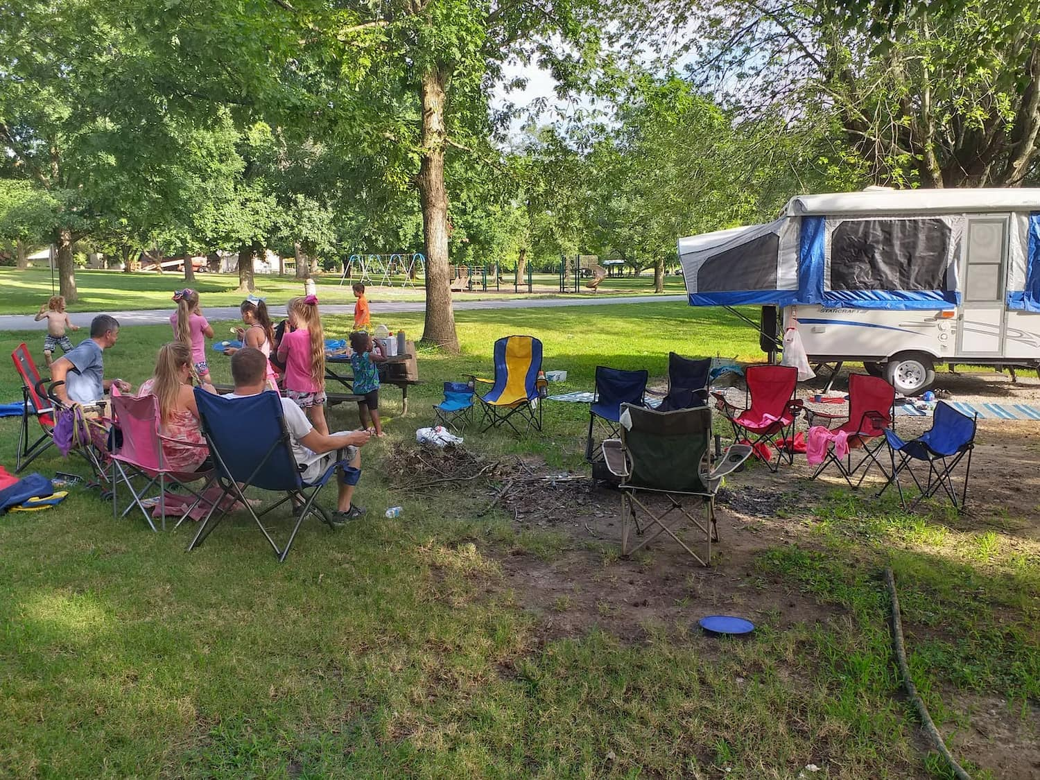 large group of families and their campchairs at campsites