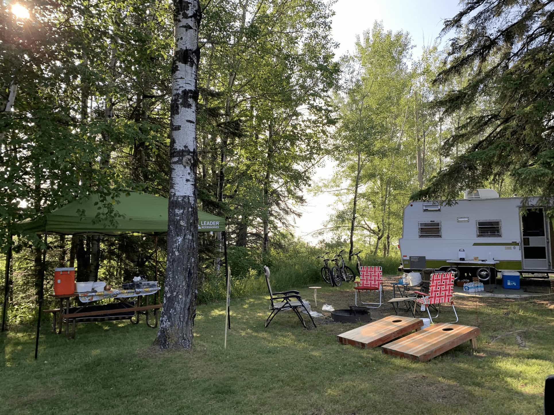 Trailer parked beside Lake Superior in a campground near Duluth complete with awning, camp chairs, and games.