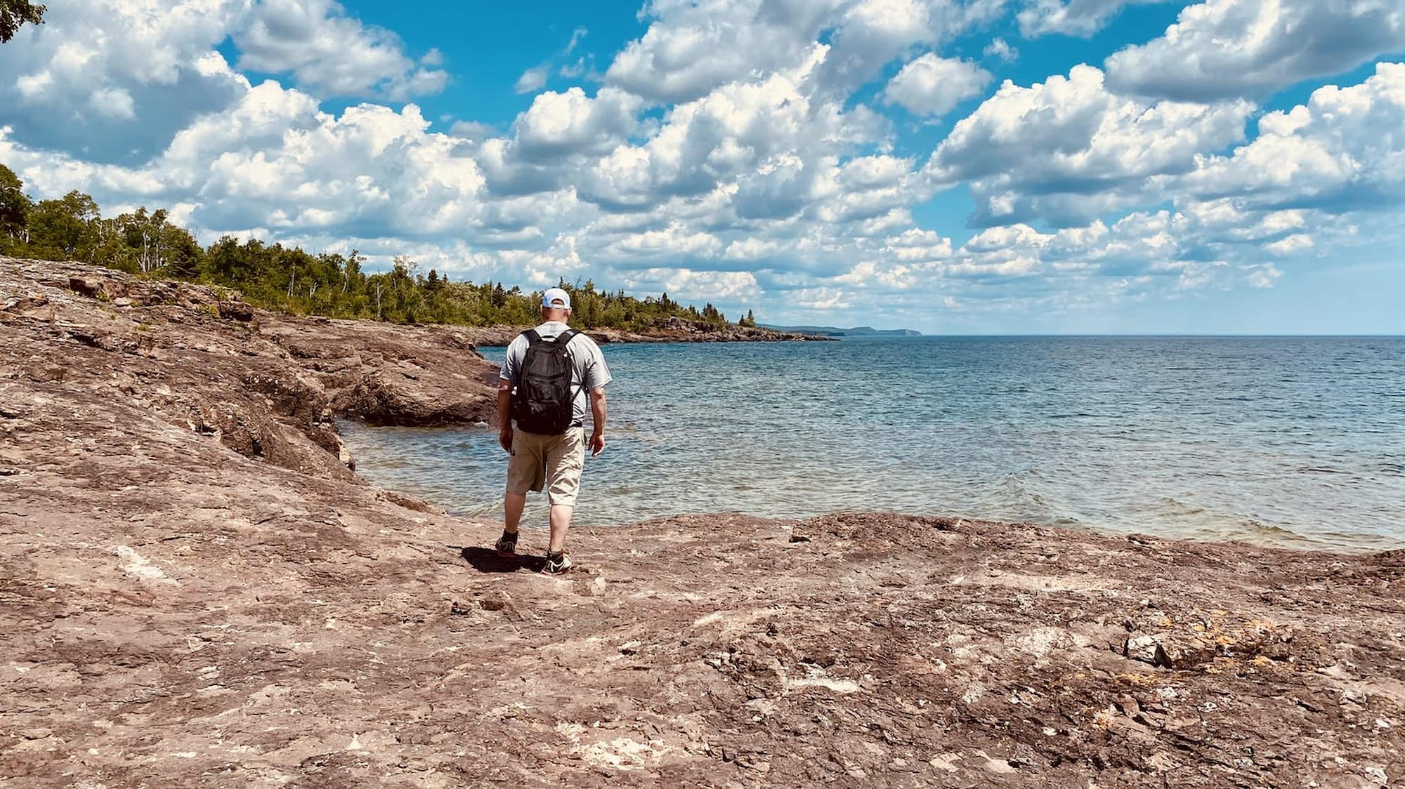 man standing on edge of the lake on a sunny day