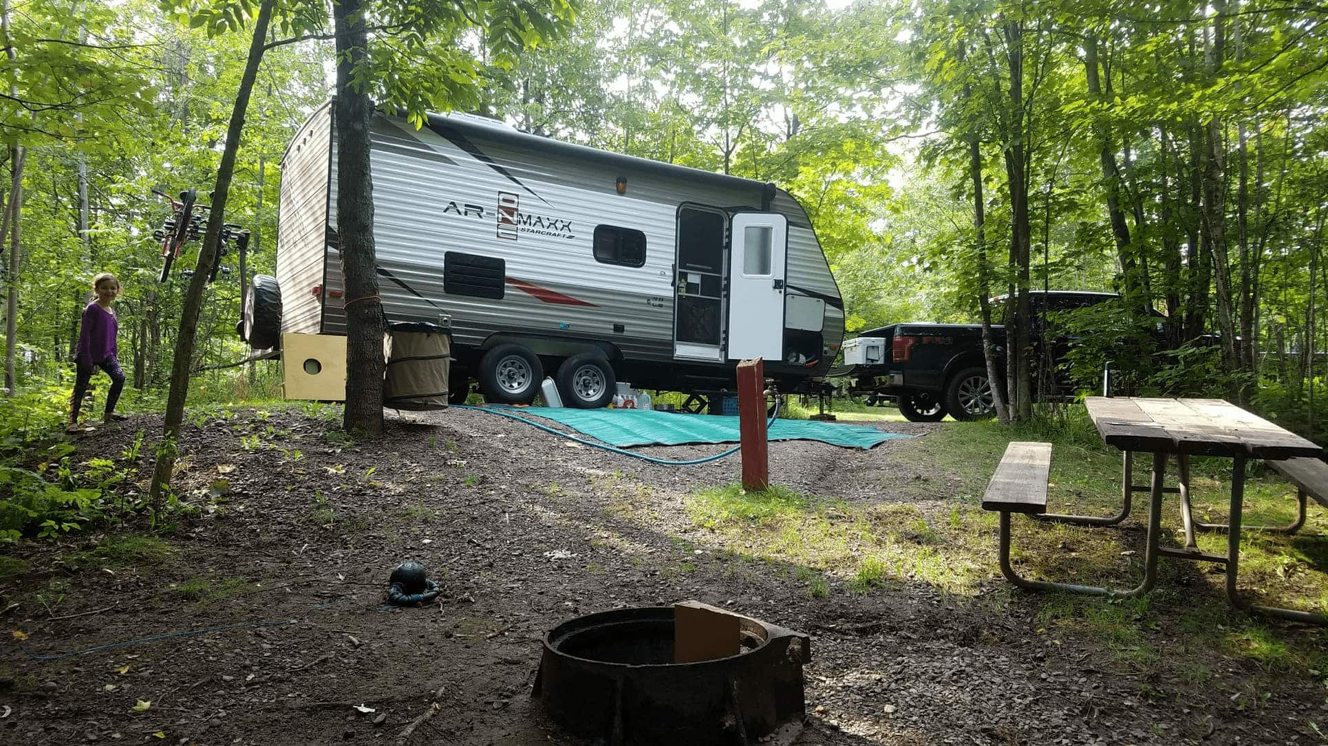 RV parked on sloped campground in the forest with a picnic table and fire pit.