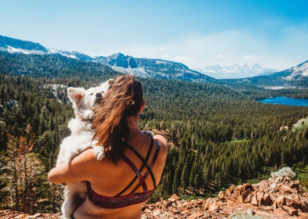 woman holding dog overlooking lake and forest