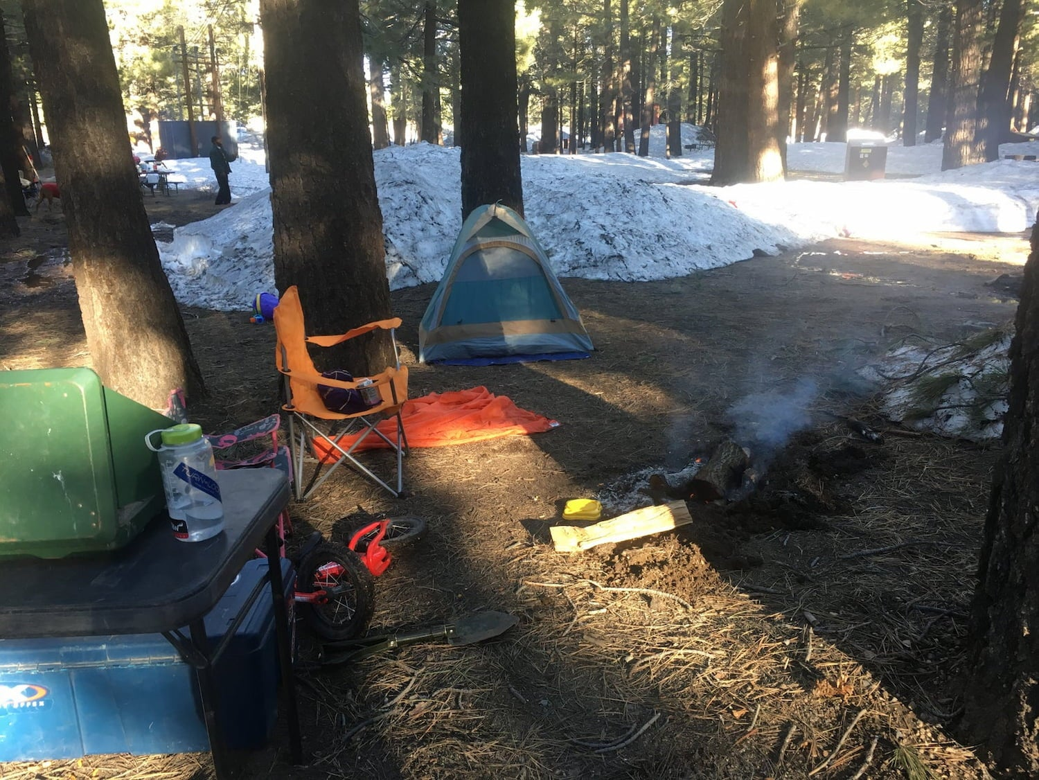 camp chairs and tent set up at campground near snow patches
