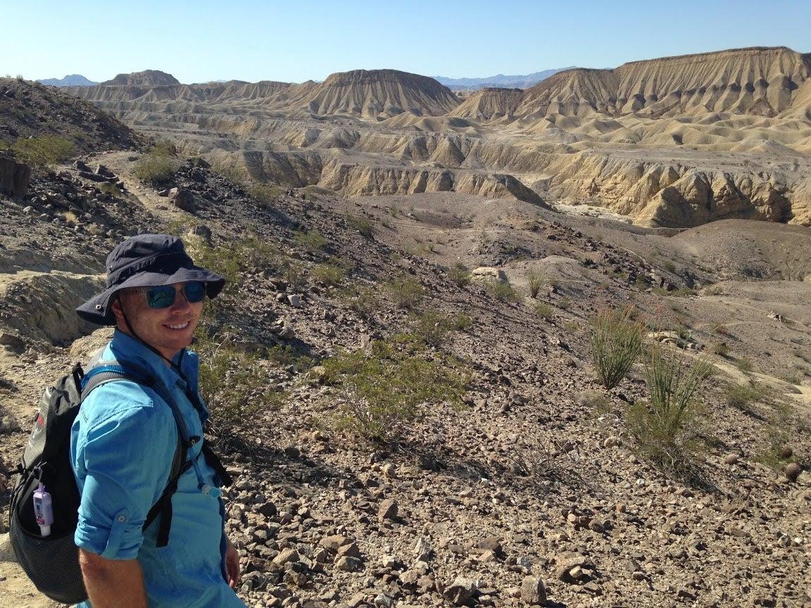 man smiling infront of desert