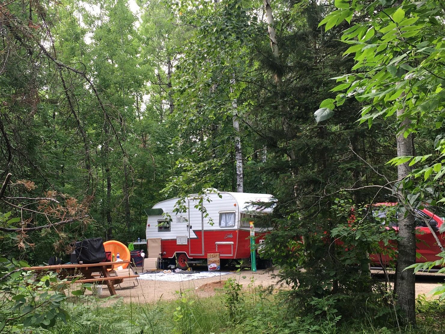 vintage pull behind camper in forest