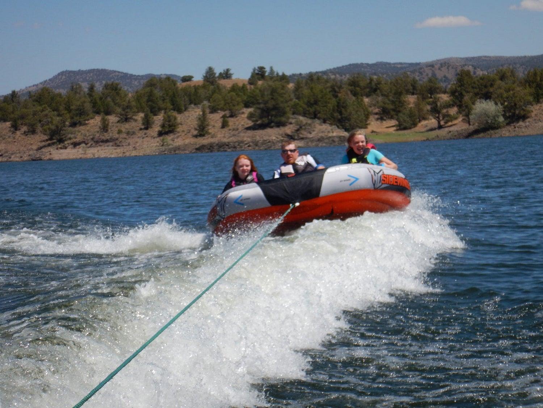 people being pulled on raft behind speedboat