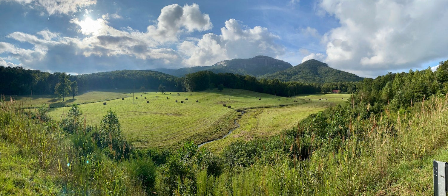 panorama of green valley and puffy clouds