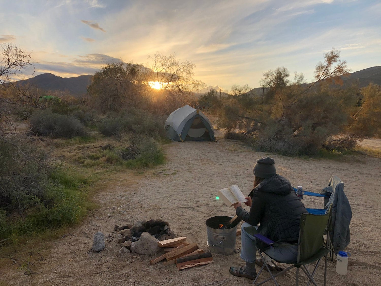 woman reading book by campfire with tent in the background
