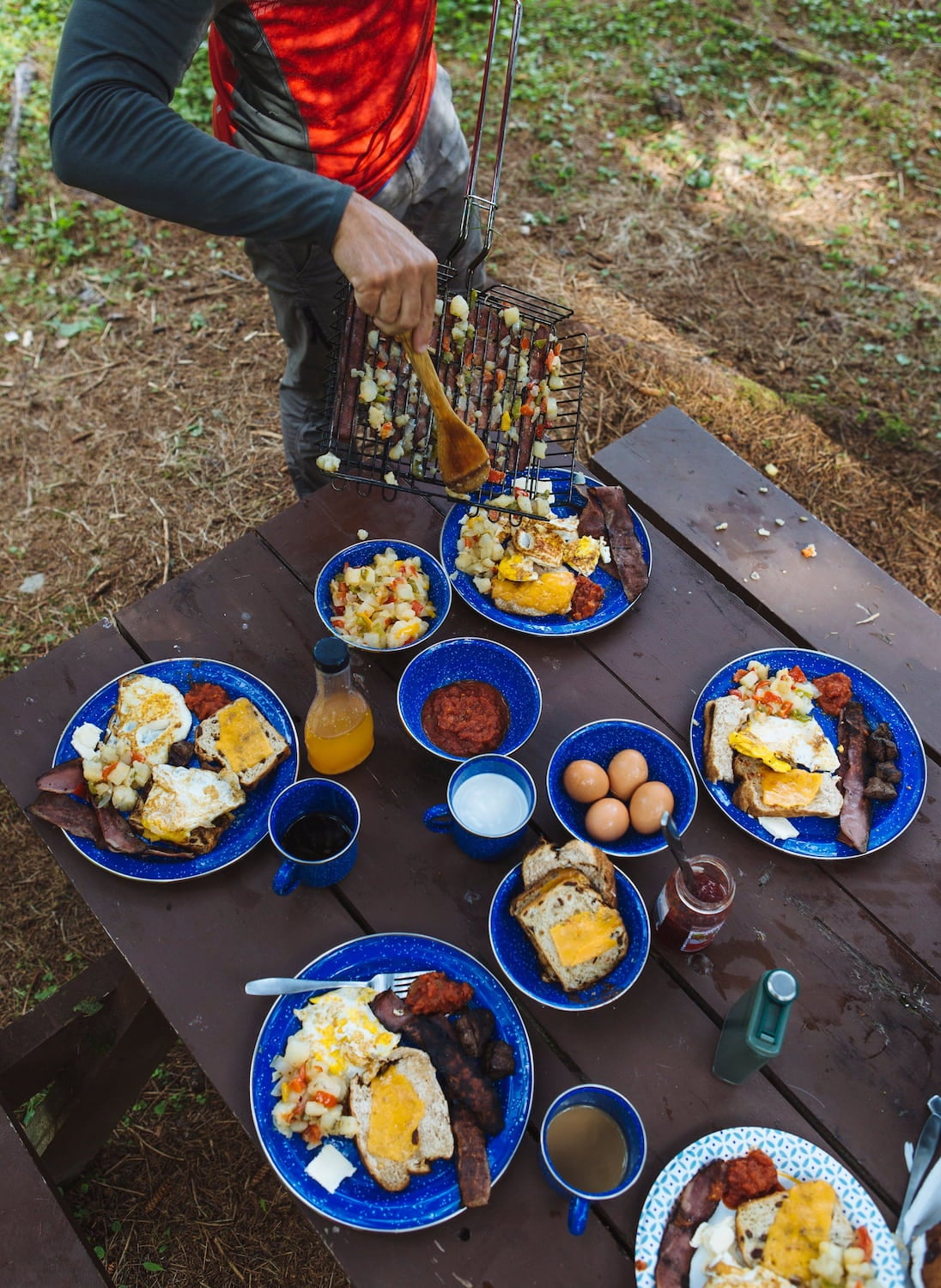 Camper plating a yummy breakfast of eggs and toast on a picnic table at a campsite.
