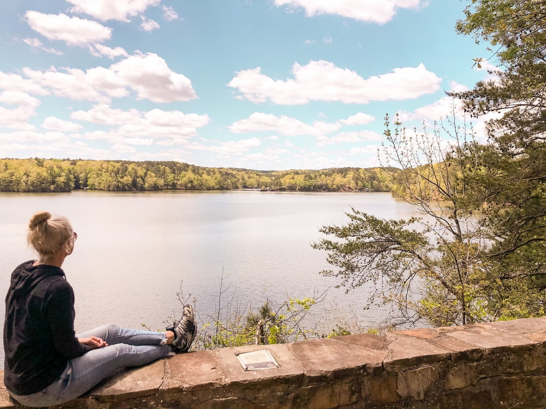 woman sitting on rockwall overlooking water