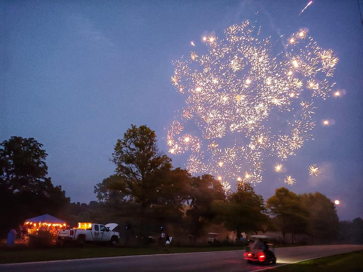 Fireworks over a campsite at night.