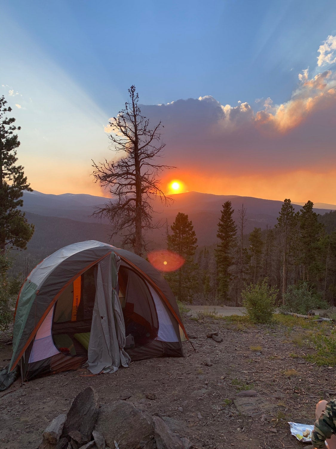 The sun setting behind a mountain with a tent at forested campsite in the foreground.