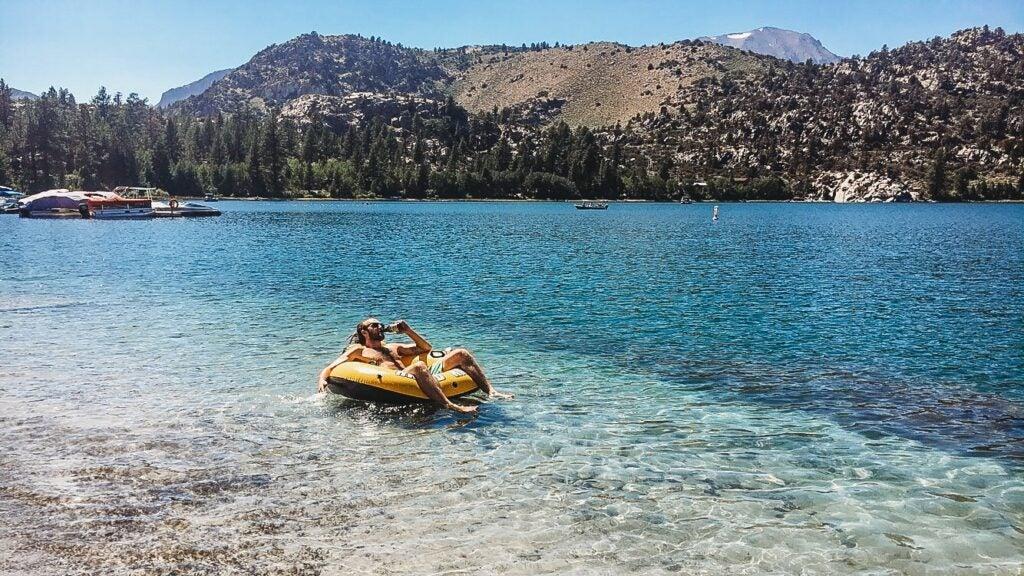 man in floaty on blue lake