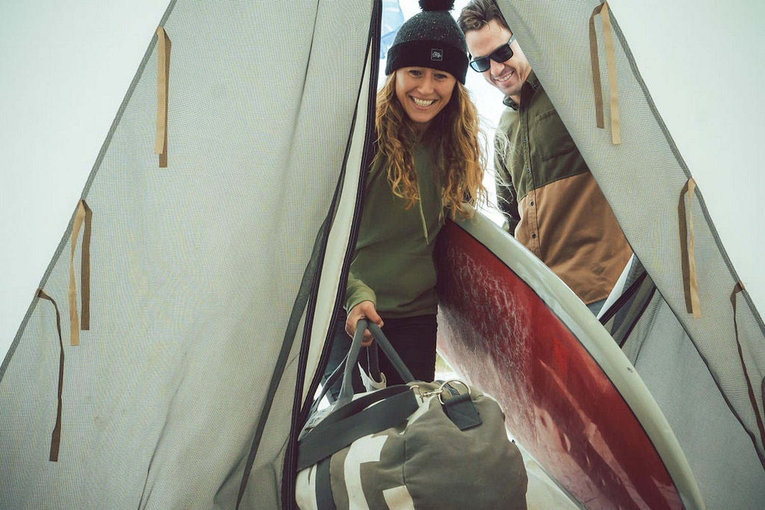 Campers walking into canvas platform tent with luggage and surfboards at rockaway.