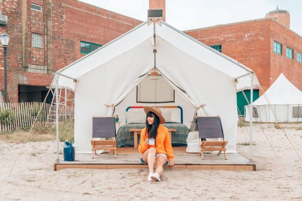 Women sitting on porch of canvas platform tent on Rockaway Beach.