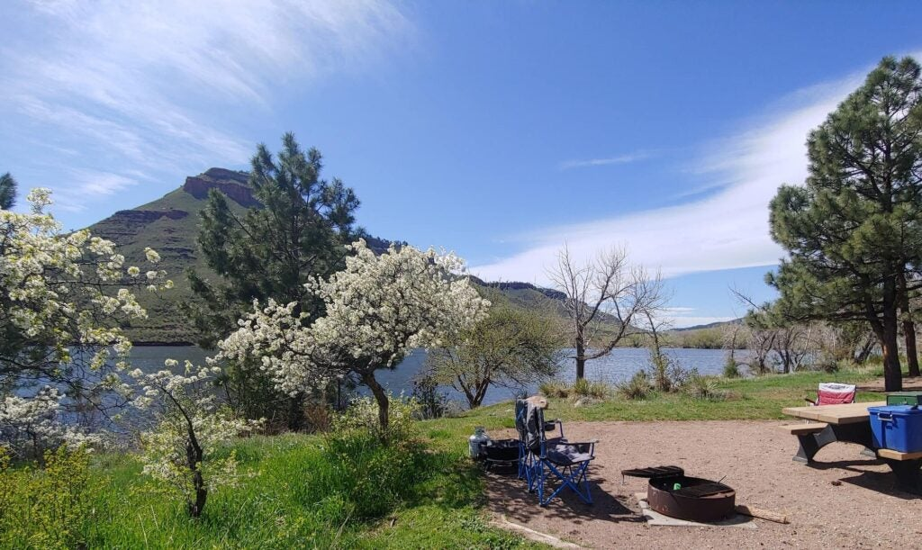 Campsite beside a flowering tree, lake and mountain in the background outside Fort Collins.