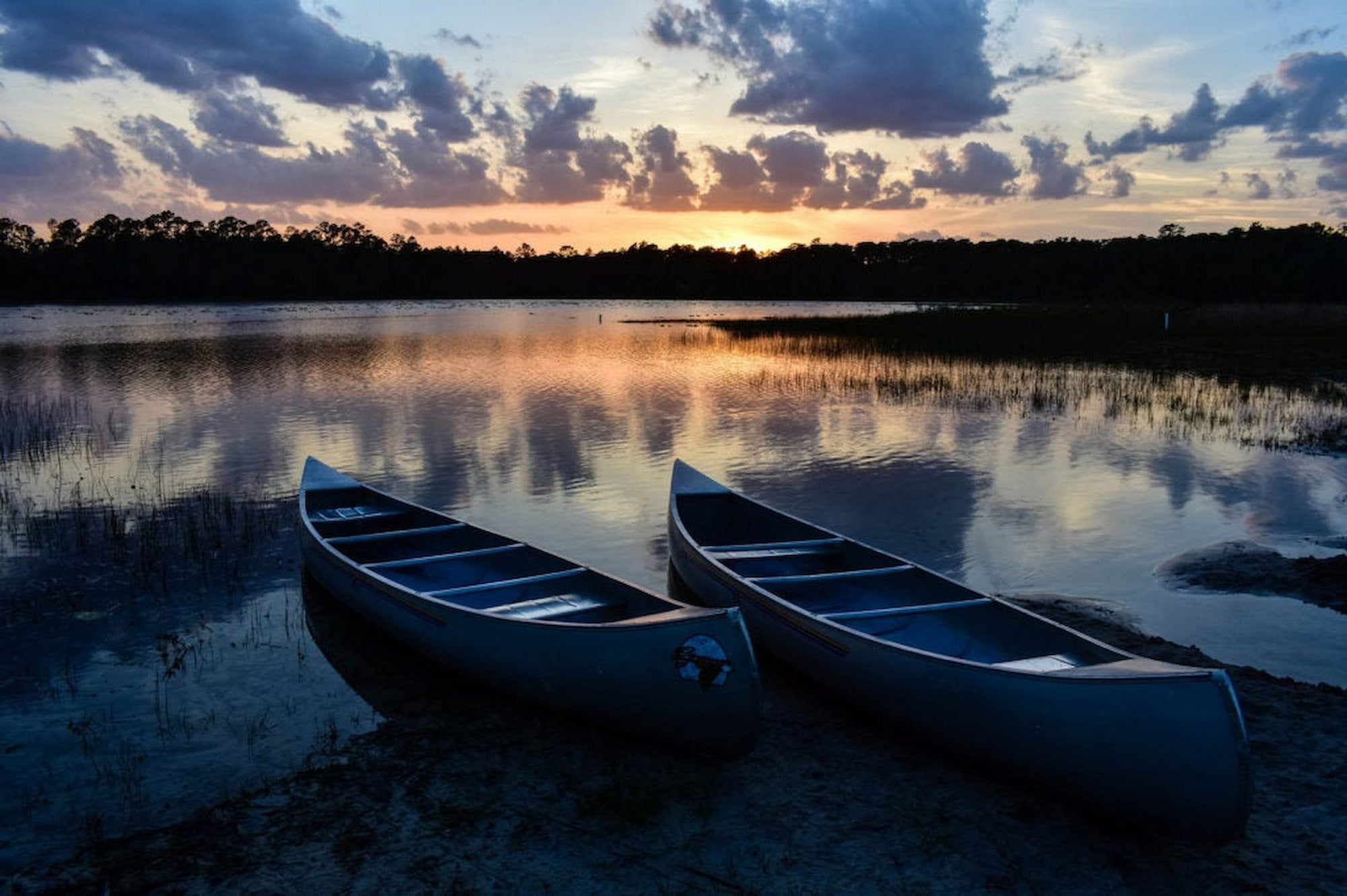 Canoes on the shore during sunset at campsite in Florida.
