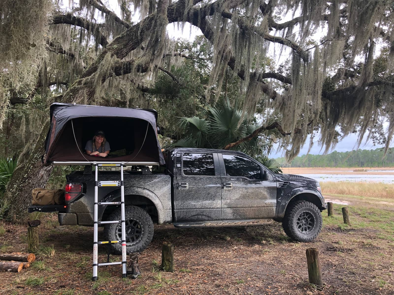 Women sitting atop her truck in a rootop tent in spanish moss of Florida.