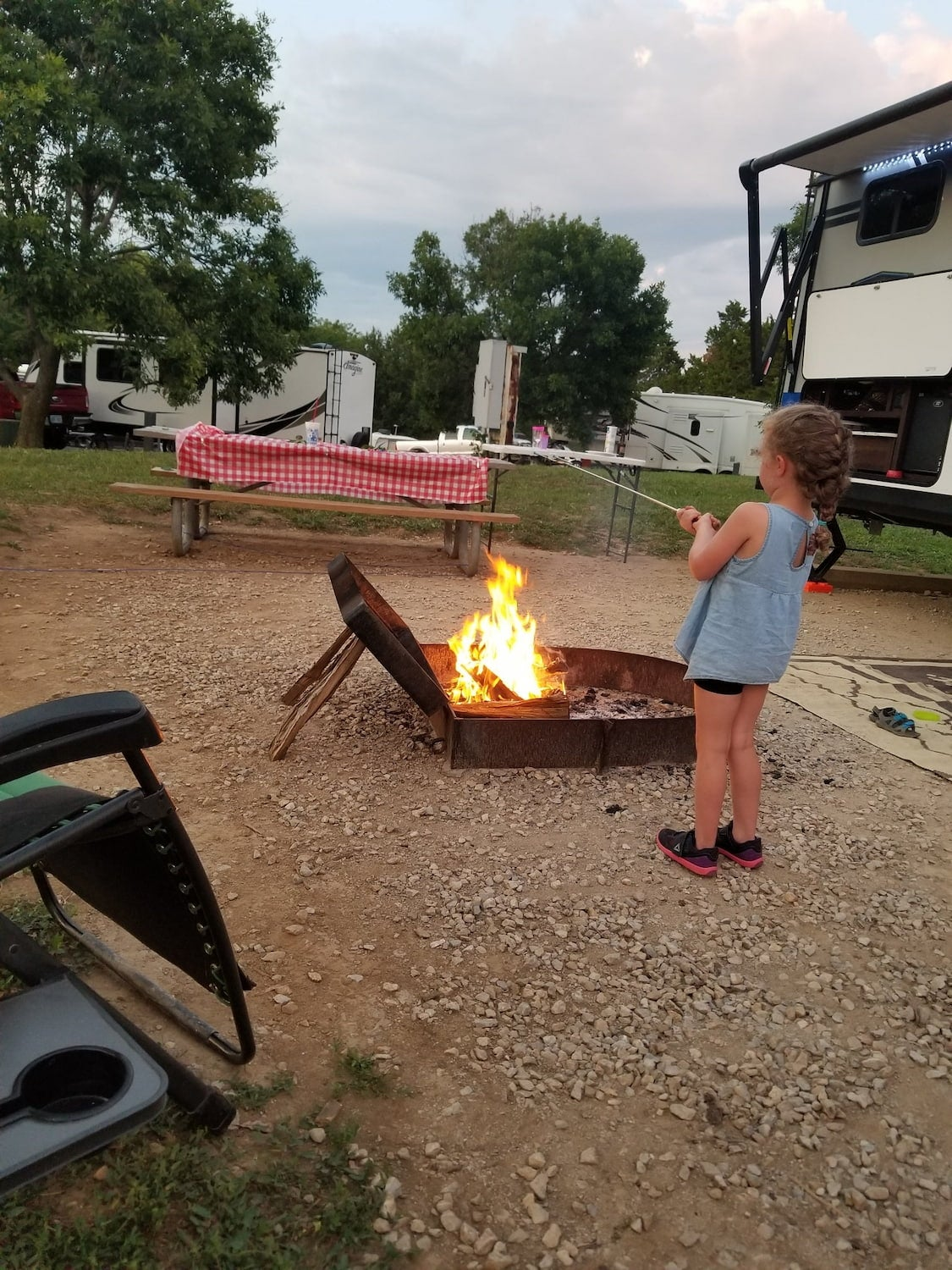 Girl holding a stick with a marhsmallow over a fire pit at an RV campsite.
