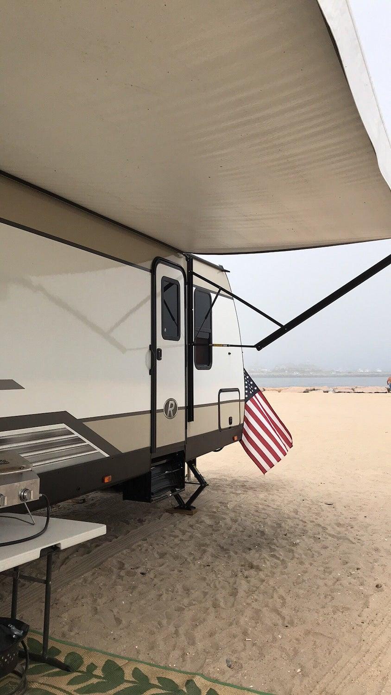 RV parked on the Rockaway beach beside the atlantic ocean.