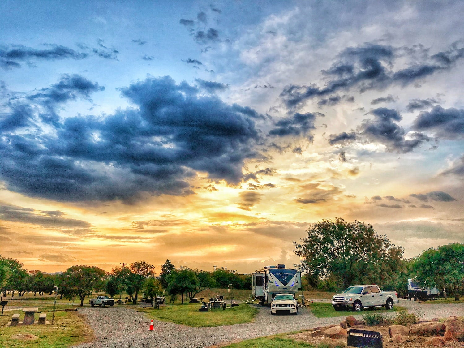 Scenic cloudy sunset over a campground with 2 trucks an RV parked.
