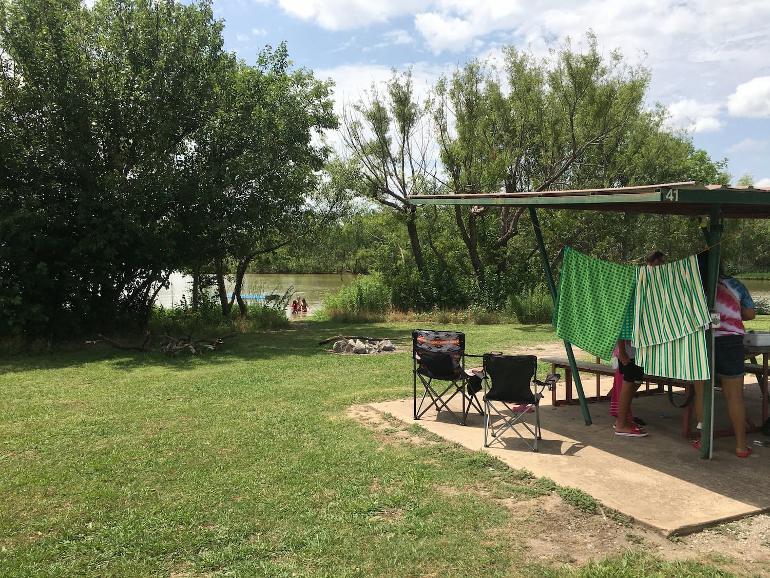 RV with awning and camp chais parked beside river where campers are swimming.