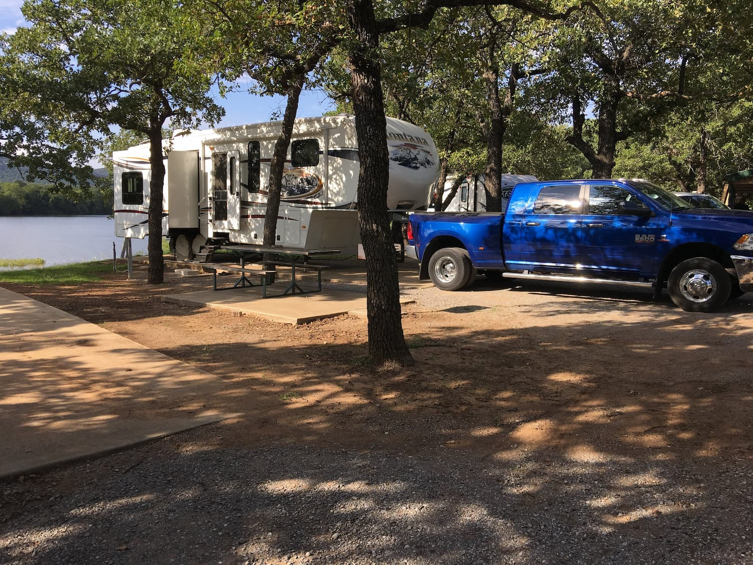RV and blue truck parked in the forest besides water at Robinson's Landing.
