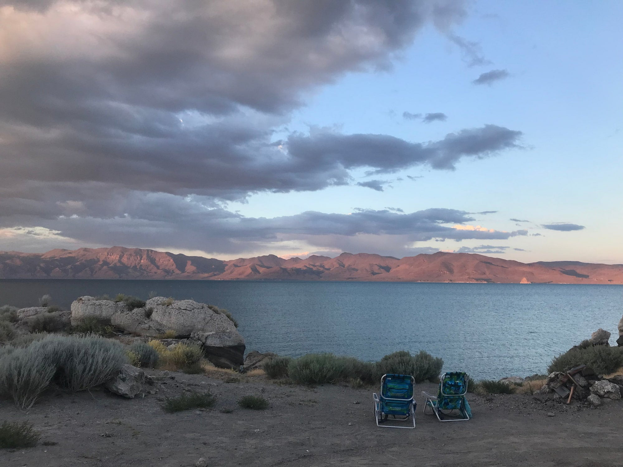 Sunset over pyramid lake campsite with beach chairs overooking the mountain landscape.