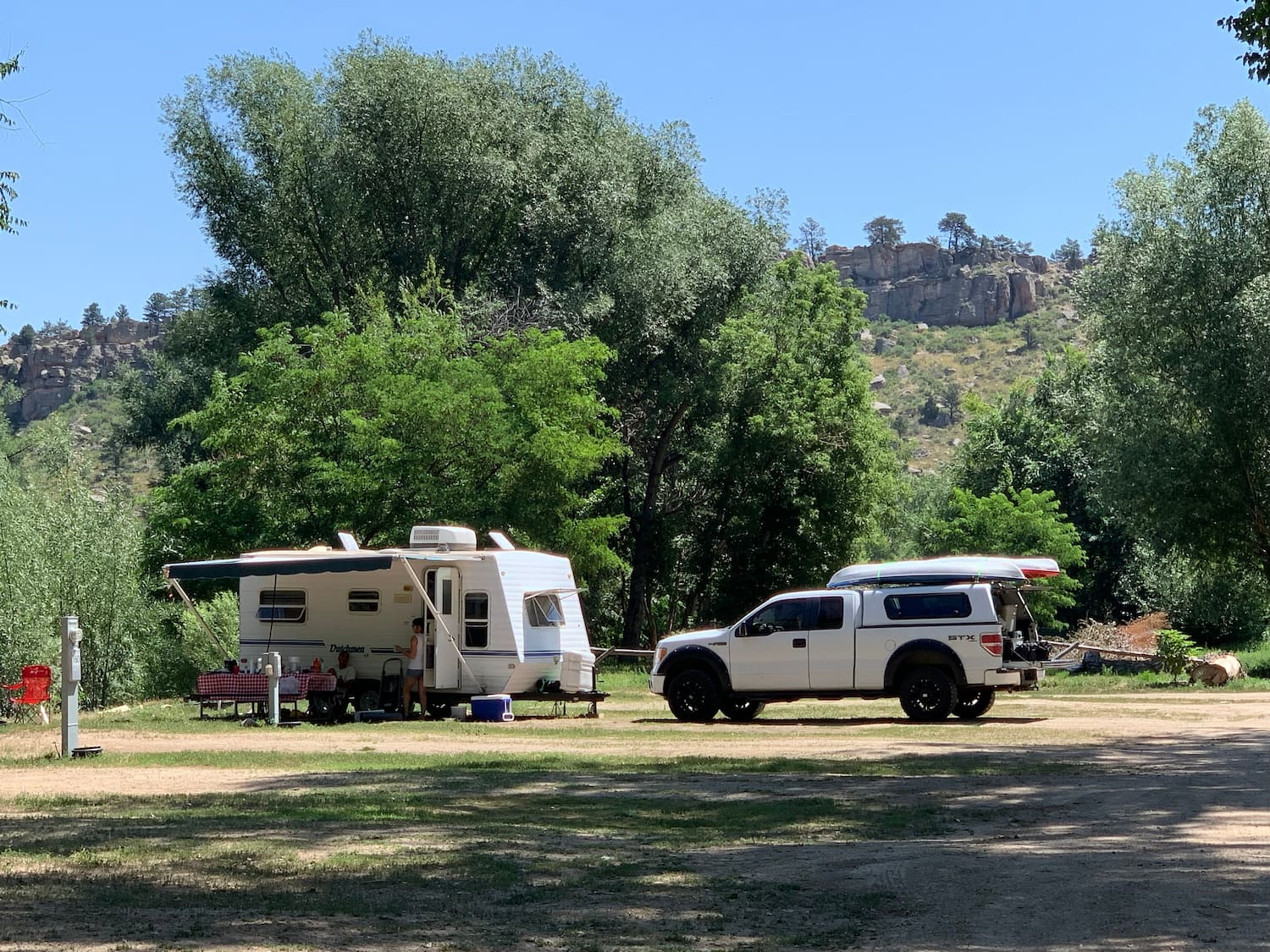 Truck and Rv parked at forested campsite near Fort Collins.