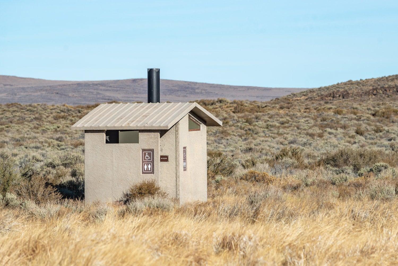 vault toilet in grassy field