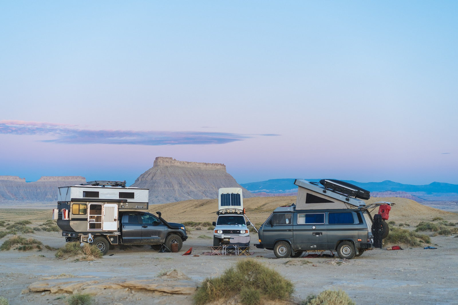 Bound for nowhre's rig parked next to two VW vans surrounded by the desert and rock formations.