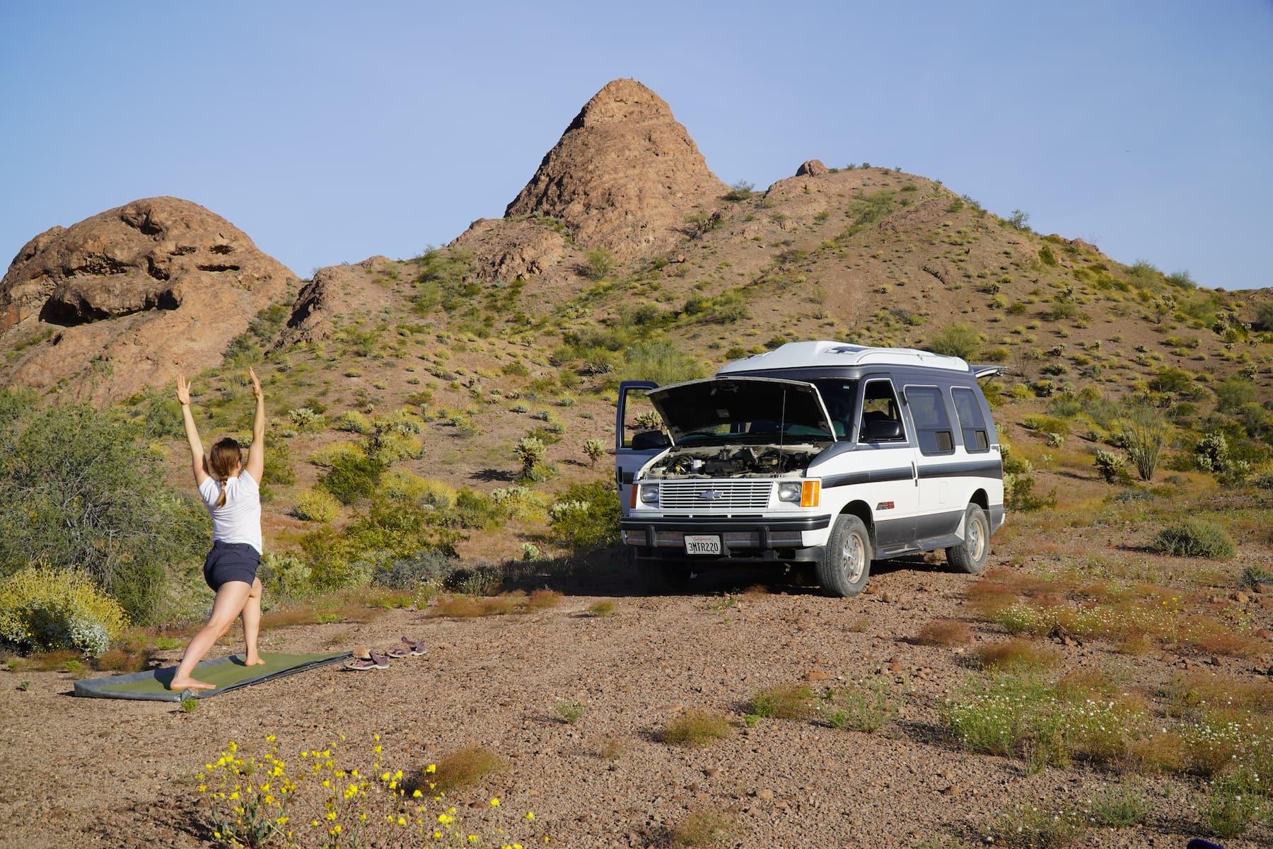Kristin Hanes founder of The Wayward Home doing yoga in front of her van in the desert.
