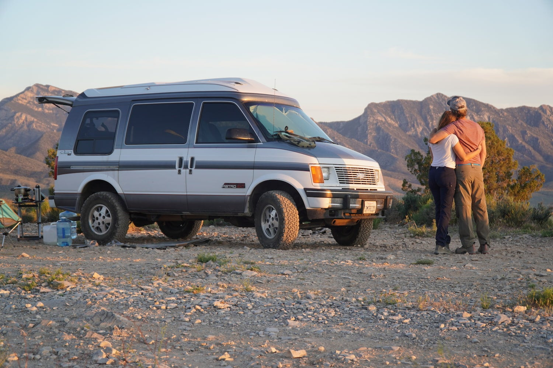 Kristin Hanes of The Wayward home and her prtner embracing beside their van in the desert.