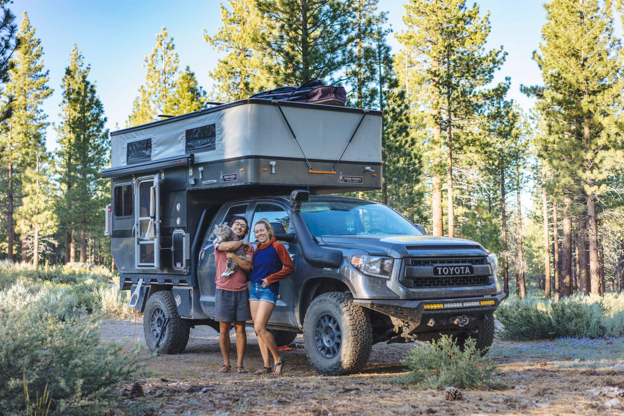 Mak and Owen of Bound for Nowhere posing outside of their full time truck camper rig with their cat.