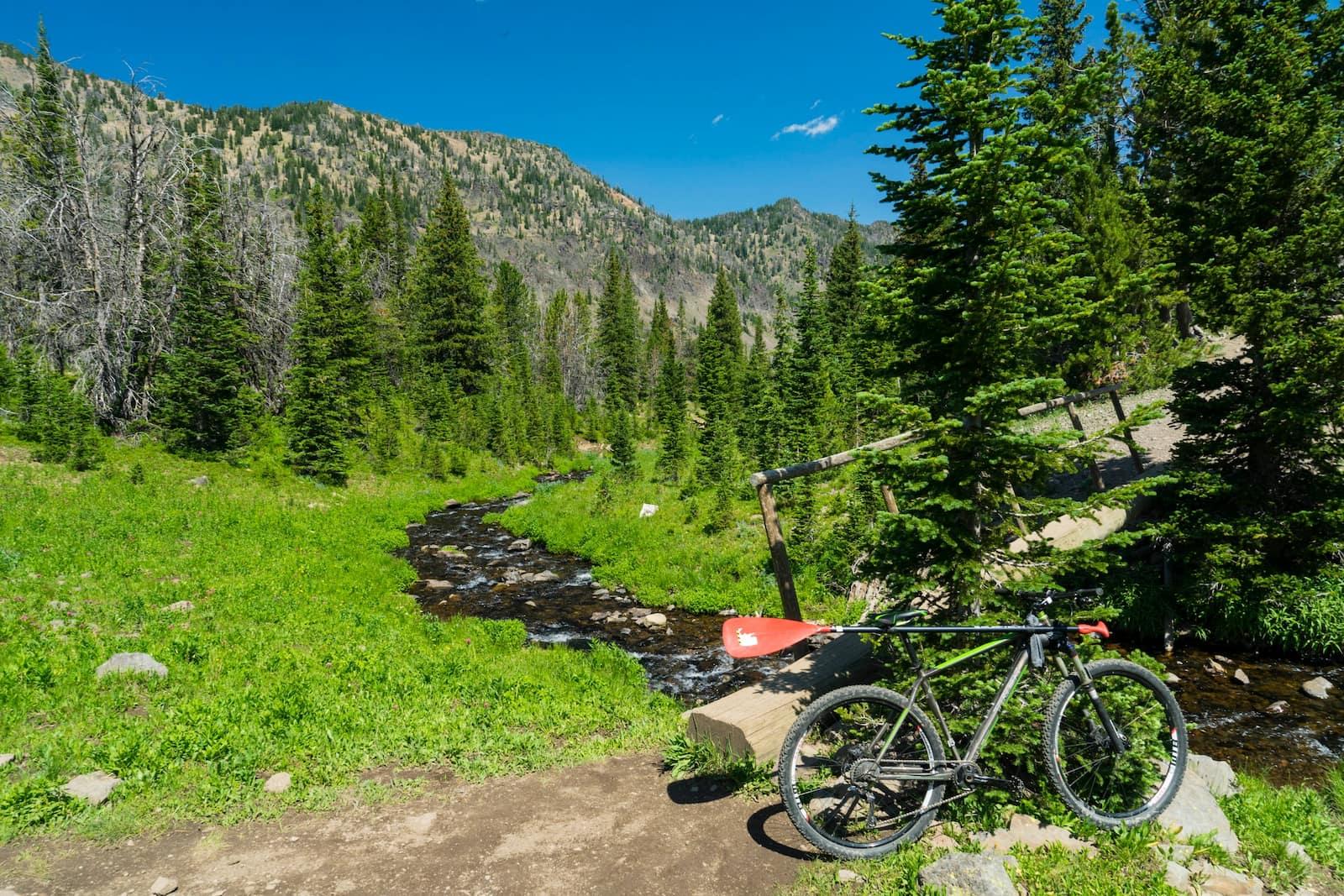 Bike with paddle next to river below Bozeman mountains.
