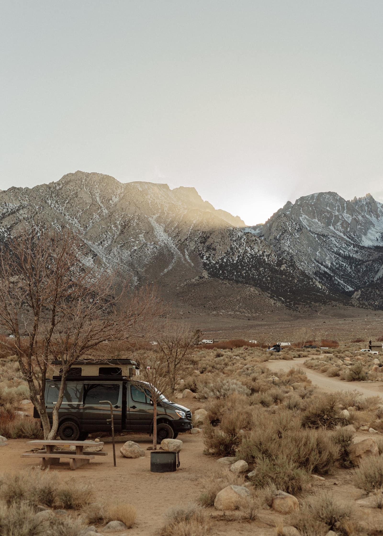 Van parked in the desert below snow covered Alabama Hills.