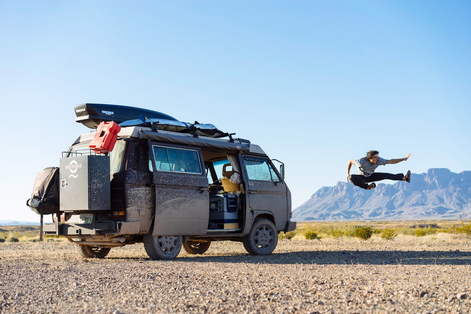 Owen from Bound for Nowhere caught in midair next to their VW Vanagon rig.