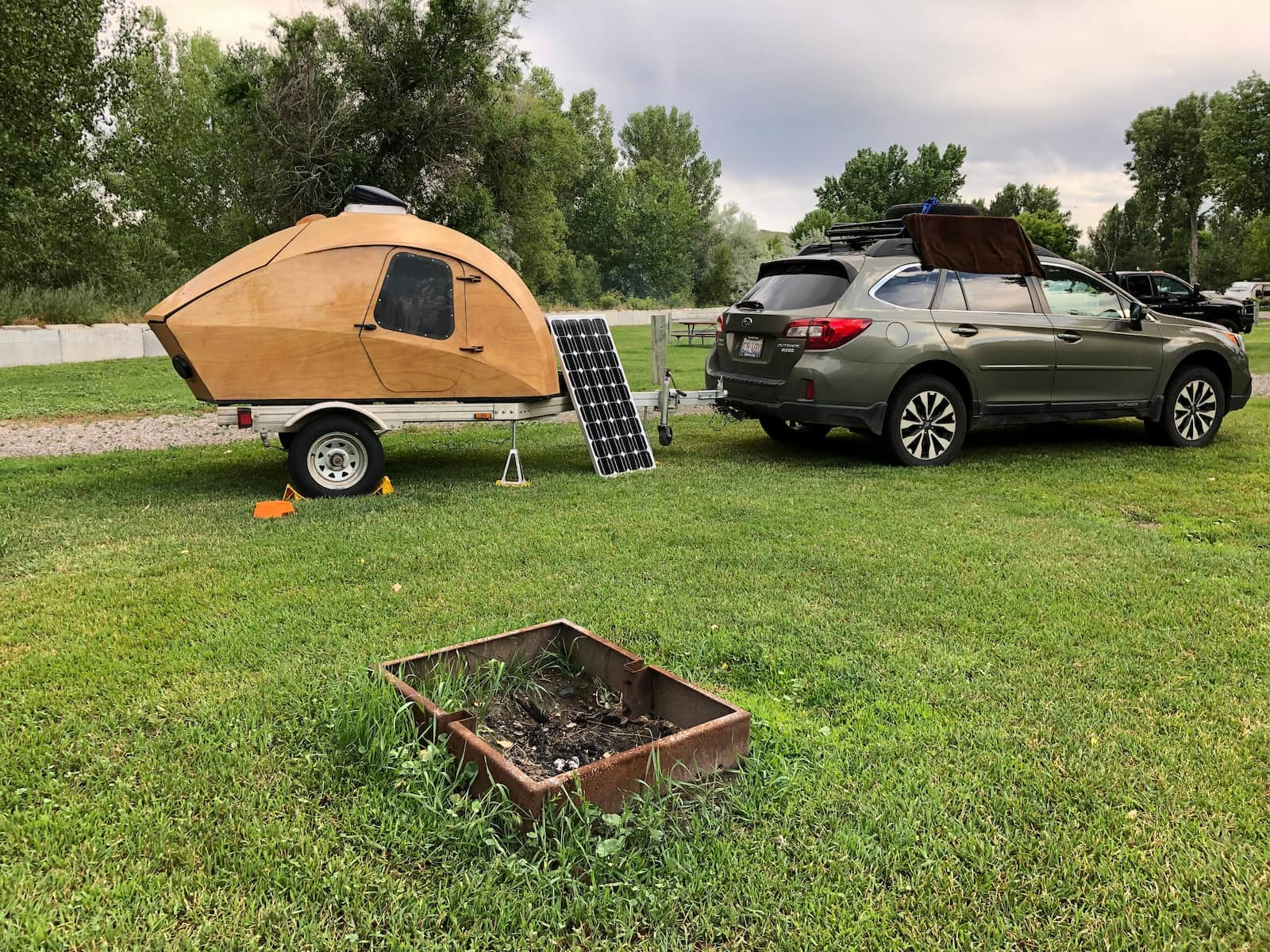 Subaru outback hooked up to wooden teardrop trailer at a campsite with square fire pit.