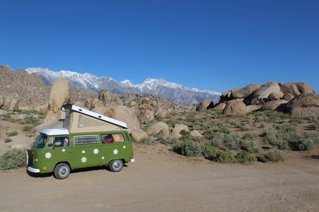 Green VW van with polka dots and pop up tent parked in the desert below Alabama hills.