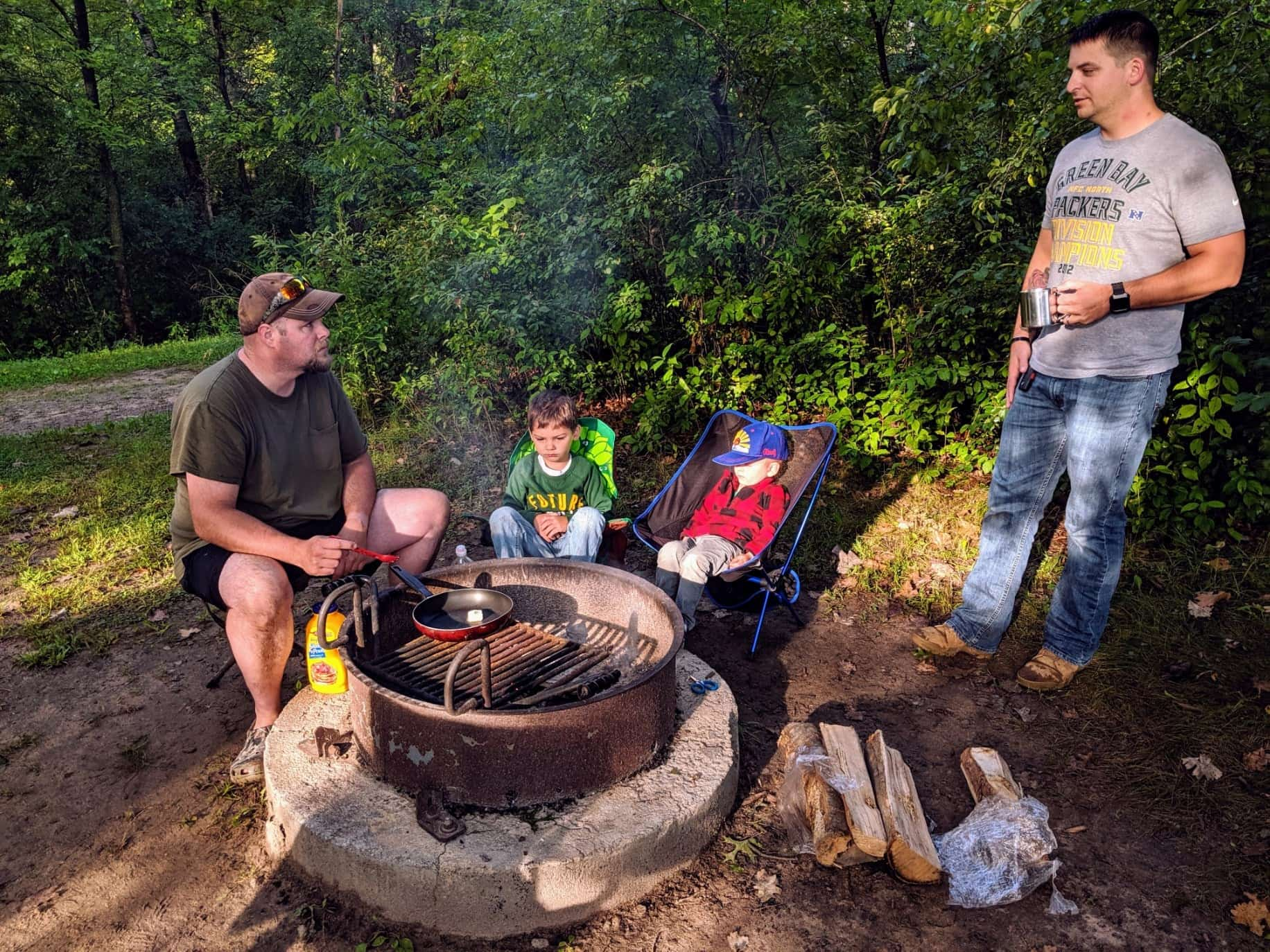 Dads and son hanging out around a fire pit at a campsite near Billings.