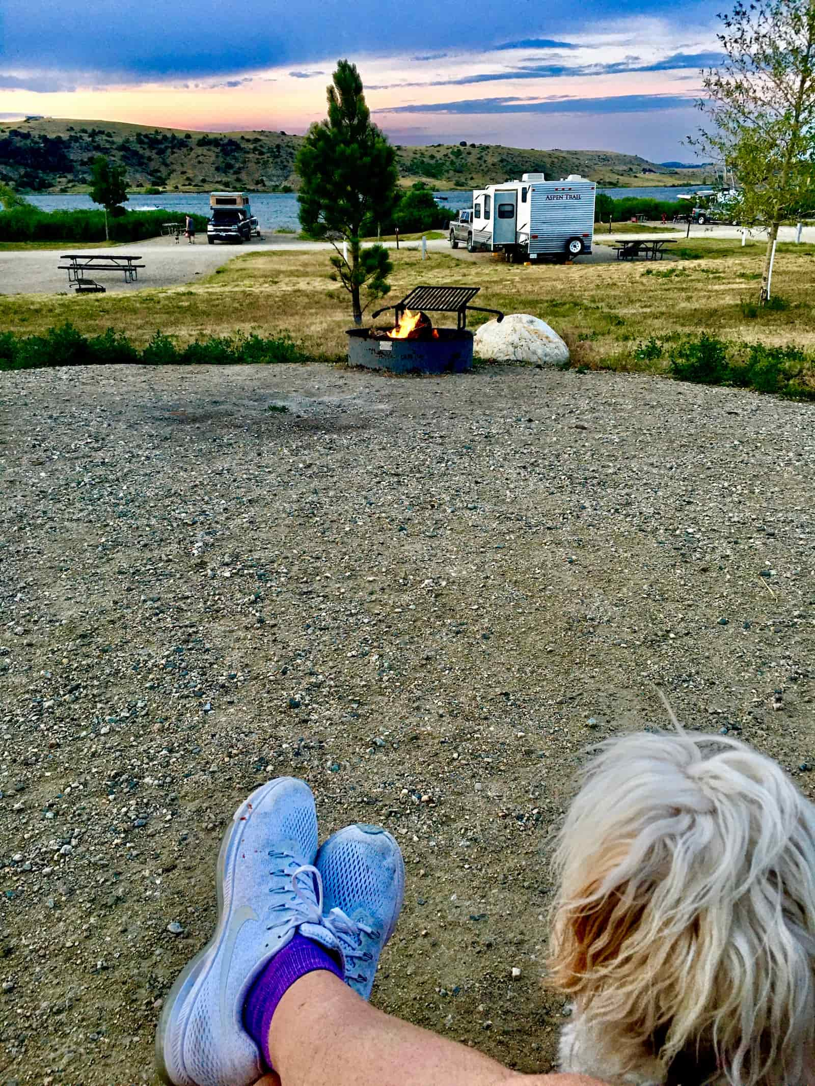 Women sitting nin front of fire with sunset and RV in the background.