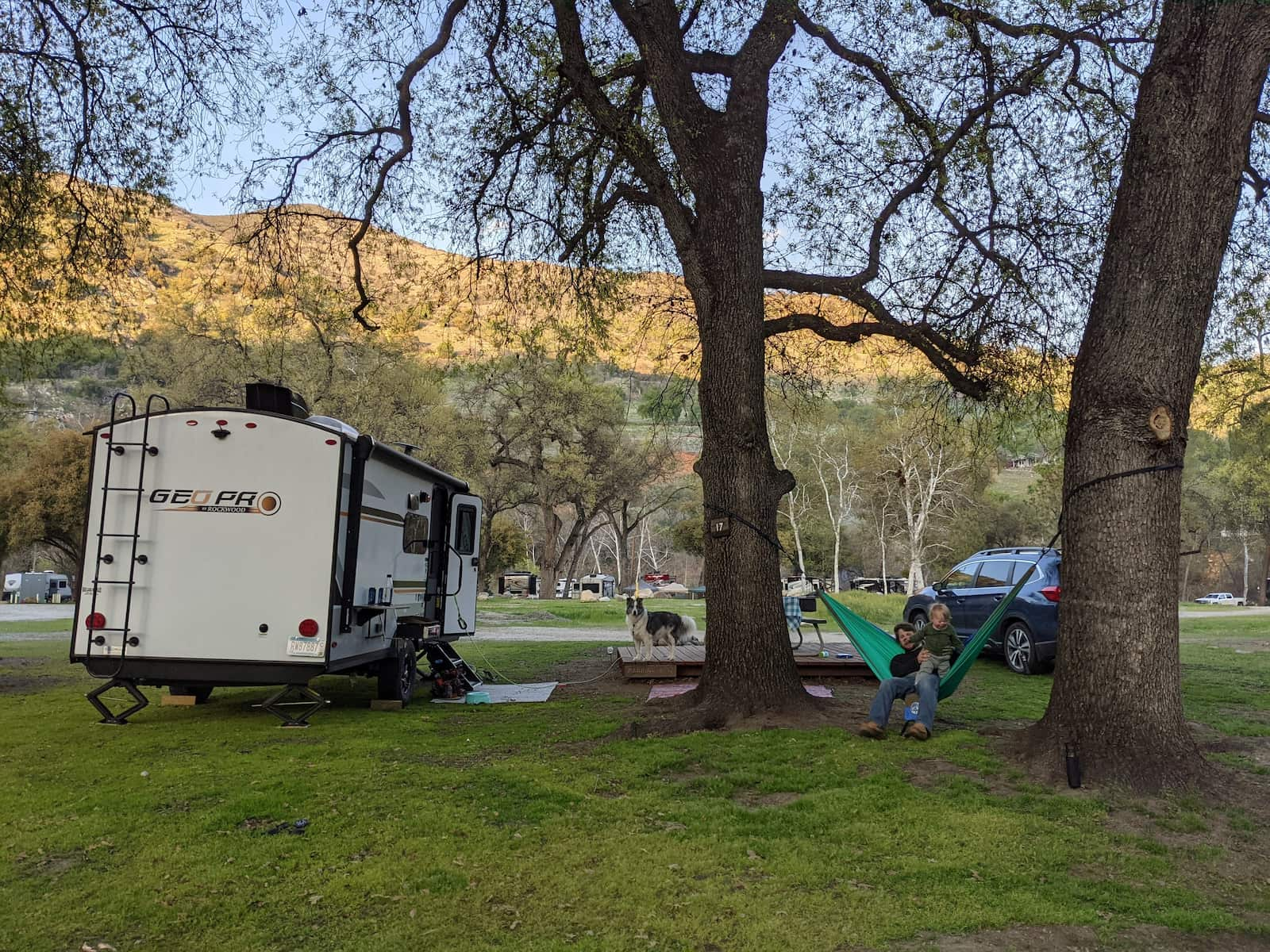 RV parked below mountains beside a tree with person hanging out in a hammock.