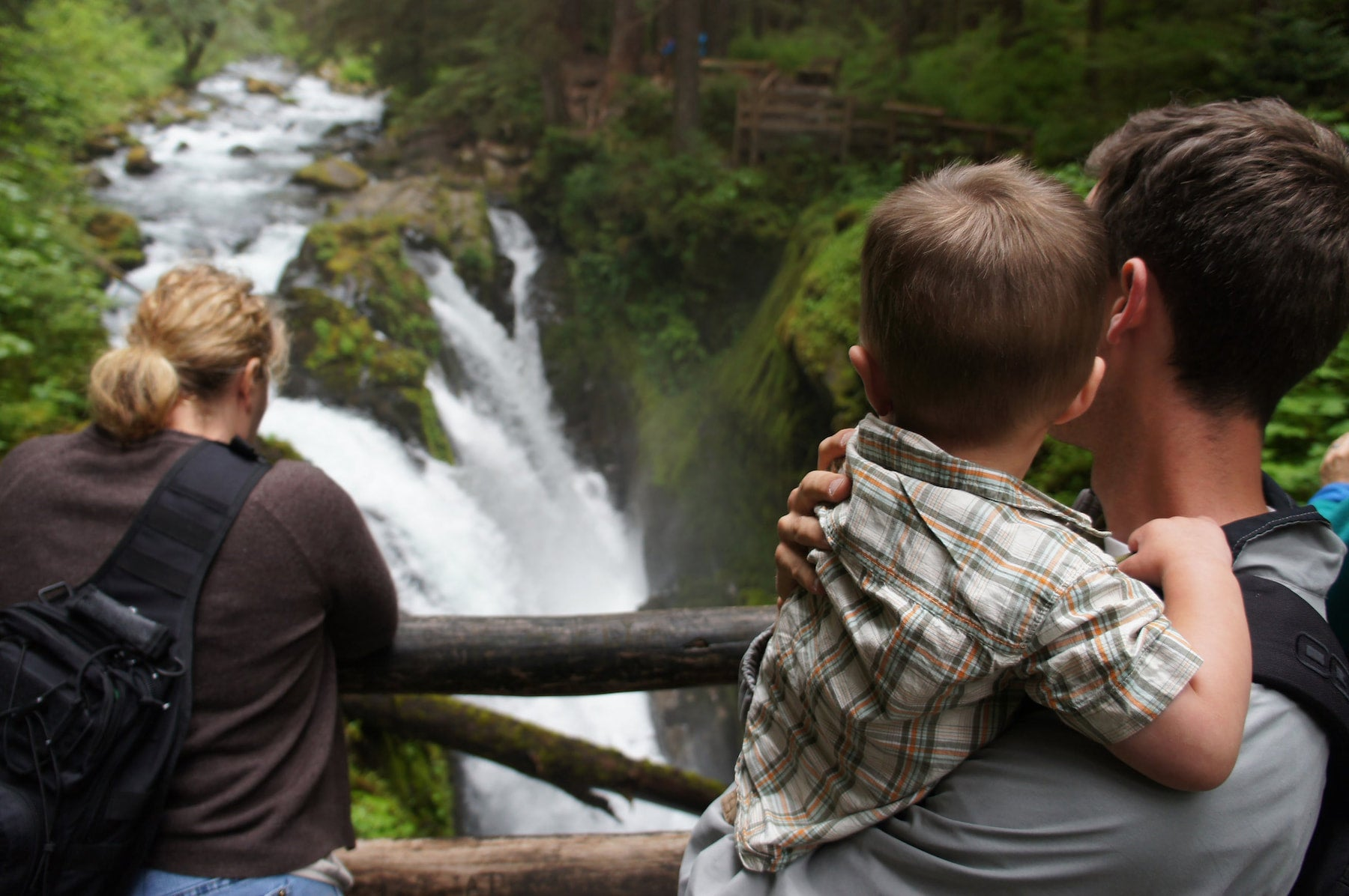 Family gathered on hiking bridge over waterfalls at Sol Duc Hot Springs Campground.